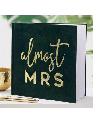 """Tummanvihreä sammettinen polttari kirja, kultaisella tekstillä """"almost MRS""""."""