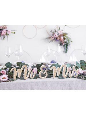 """Valkoinen puinen kyltti """"Mr & Mrs"""" kultaglitterillä."""
