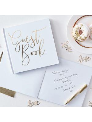 """Valkoinen vieraskirja kultaisella tekstillä """"Guest Book""""."""