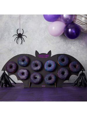 """Kiiltävä ruusukultainen donitsiseinä tekstillä """"Donuts""""."""